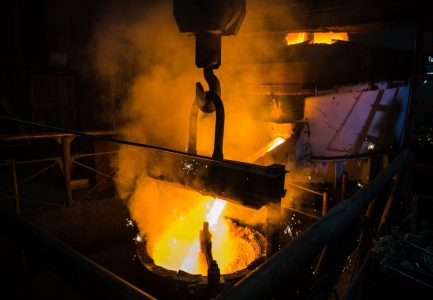 Molten steel pouring. Liquid hot metal of steel spills out of the ladle at steel factory
